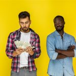 european guy is counting money and afroamerican guy is humiliating looking at him in informal clothes on the yellow background