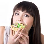 Young beautiful hungry woman eating very delicious tart cake with covered in cream face. Diet failure concept. Studio, white background, isolated