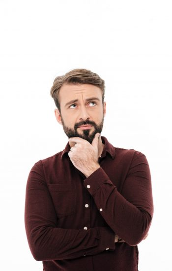 Portrait of a pensive handsome man looking away at copy space with hand on her chin isolated over white background