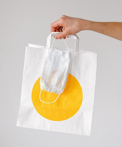 person-holding-paper-bag-and-face-mask-3987245